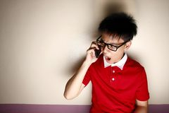 Angry Teenage kid talking on a smartphone Royalty Free Stock Image