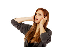 Angry teenage woman covering ears with hands Stock Photos