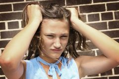 Angry teenager. Teenager girl looking very angry and having hand in hair Stock Images
