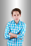 Angry teenager looking in front of his eyes with his arms folded. Royalty Free Stock Image