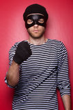 Angry thief. Classic thief standing at the red background royalty free stock image