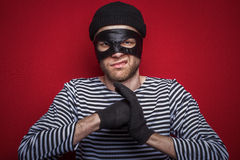 Angry thief. Classic thief standing at the red background stock images