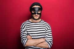 Angry thief with mask. On red background Royalty Free Stock Photos