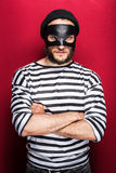 Angry thief with mask. On red background Stock Photo