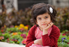 Angry and Thoughtful Little girl in the Garden Royalty Free Stock Image