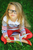 Angry and tired little girl with a book in a park Royalty Free Stock Image
