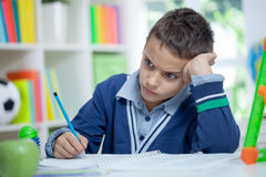 Angry and tired schoolboy studying Stock Photo