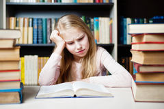 Angry and tired schoolgirl studying with a pile of books Stock Image