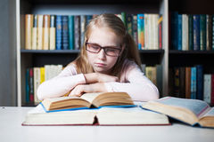 Angry and tired schoolgirl studying with a pile of books Royalty Free Stock Photography