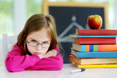 Angry and tired schoolgirl studying with a pile of books on her desk Royalty Free Stock Photography