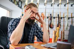 Angry and tired young hipster sit at table in room. He hold hands close to head. Guy has headache. Many electric guitars. Hanging behind him stock photos