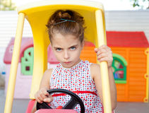 Angry toy car driver children girl. In playground Stock Image