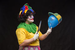 Angry ugly clown wants to kill a balloon in the cap Stock Photography