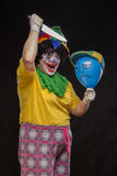 Angry ugly clown wants to kill a balloon in the cap Royalty Free Stock Photo