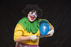 Angry ugly clown wants to kill a balloon in the cap Royalty Free Stock Image