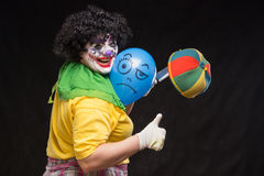 Angry ugly clown wants to kill a balloon in the cap Stock Photos