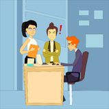 Angry unhappy boss standing next to the table of her afraid employee in the office. Royalty Free Stock Image