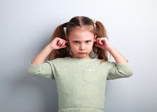 Angry unhappy kid girl coverd ears the fingers and gesturing tha. T not want to listen on blue background with empty copy space Royalty Free Stock Images