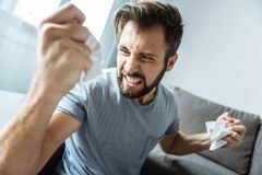 Angry unhappy man clenching his teeth. Emotion of anger. Unhappy brutal bearded man clenching his teeth and looking at his hand while crumpling paper Stock Photos