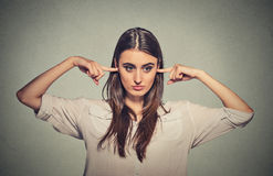 Angry unhappy woman with closed ears looking away. Closeup portrait young angry unhappy woman with closed ears looking away annoyed by loud noise giving her Royalty Free Stock Image