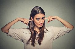 Angry unhappy woman with closed ears looking at you Stock Images