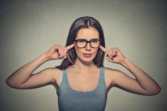 Angry unhappy woman with glasses plugging ears with fingers Royalty Free Stock Photography