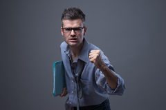 Angry untidy businessman. With files snarling with fist raised Royalty Free Stock Photography