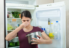 Angry and upset housewife looking into pot with foul meal Royalty Free Stock Image