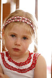 Angry and upset little girl. Close up of blonde haired and blue eyed little girl upset looking at camera Stock Image