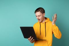 Angry upset maneger in yellow hoodie holding laptop and screaming stock images