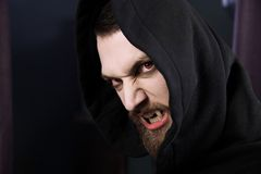 Angry vampire with red eyes. Male vampire ready to attack and eat blood Stock Photos