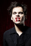 Angry vampire showing his teeth. Blood is flowing down at the side of his mouth Stock Photos