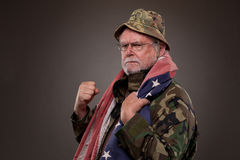 Angry Vietnam Veteran with American flag. Vietnam Veteran with American flag around his neck royalty free stock photo