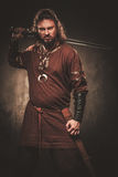 Angry viking with sword in a traditional warrior clothes, posing on a dark background. Stock Photo