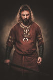 Angry viking with sword in a traditional warrior clothes, posing on a dark background. Royalty Free Stock Images