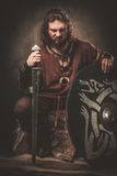 Angry viking with sword in a traditional warrior clothes, posing on a dark background. Royalty Free Stock Photo