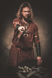 Angry viking with sword in a traditional warrior clothes, posing on a dark background. Royalty Free Stock Image