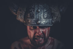 Angry Viking warrior with a horned helmet and war paint on his f Stock Photos