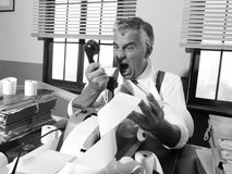 Angry vintage businessman shouting at phone. Angry vintage businessman shouting out loud at phone surrounded by adding machine tape Stock Images