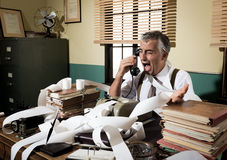 Angry vintage businessman shouting at phone. Angry vintage businessman shouting out loud at phone surrounded by adding machine tape Royalty Free Stock Photography