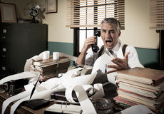 Angry vintage businessman shouting at phone. Angry vintage businessman shouting out loud at phone surrounded by adding machine tape Royalty Free Stock Photos