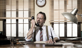 Angry vintage businessman shouting on the phone. Working at office desk Royalty Free Stock Photo