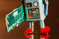 Tin toy robot carries computer circuit board, artificial intelligence concept. Angry vintage tin toy robot carries green computer circuit board, artificial Stock Image