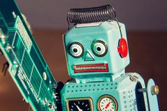 Tin toy robot carries computer circuit board, artificial intelligence concept Royalty Free Stock Image