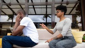 Angry wife blaming upset stressed black man turned away ignoring annoying wife. Unhappy african family couple arguing, angry wife blaming upset stressed black royalty free stock images