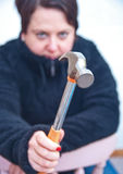 Angry wife with hammer. Domestic violence when angry wife raises hammer to strike Royalty Free Stock Images