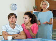 Angry wife and mother-in-law rebuking young man Royalty Free Stock Photography