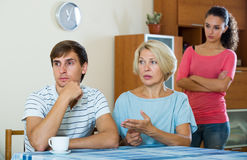 Angry wife and mother-in-law rebuking young man. Adult guy having argue with wife and mother-in-law Stock Photo