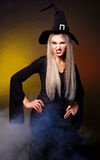 Angry witch. Angry young blond witch with  clouds of blue smoke around her,against black background Royalty Free Stock Photography