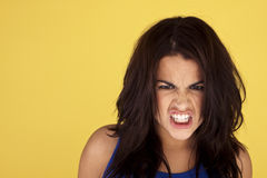 Angry woman. Head-shot of a young and angry woman on a yellow background Royalty Free Stock Photo